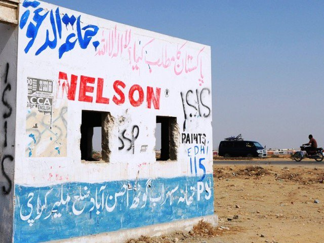 In this photograph taken on October 16, 2014 shows motorists driving past an empty police check post with graffiti which reads as ISIS along a street on the outskirts of Karachi. PHOTO: AFP