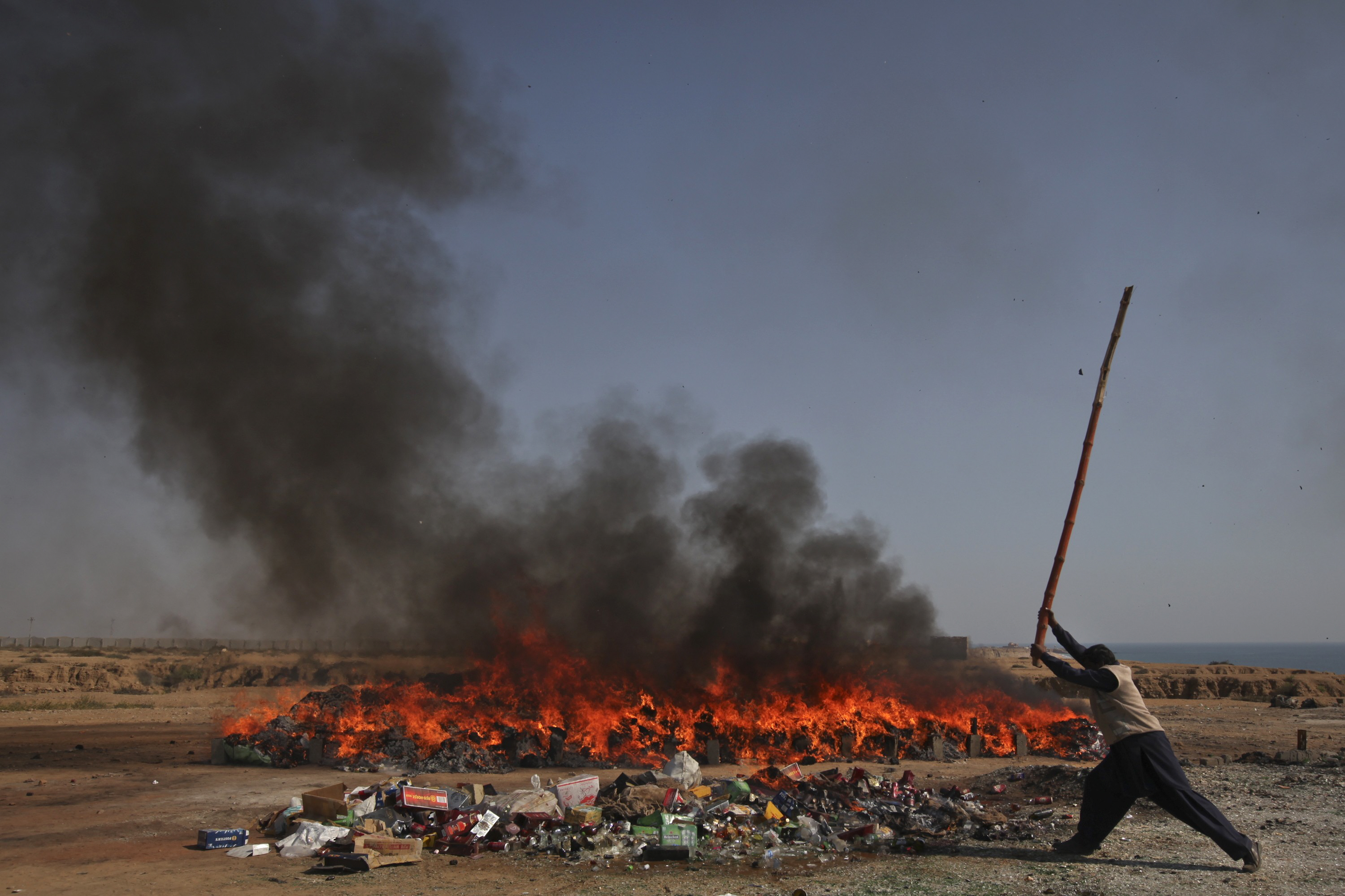 A man from the customs uses a bamboo stick to destroy bottles of liquor. PHOTO: AFP