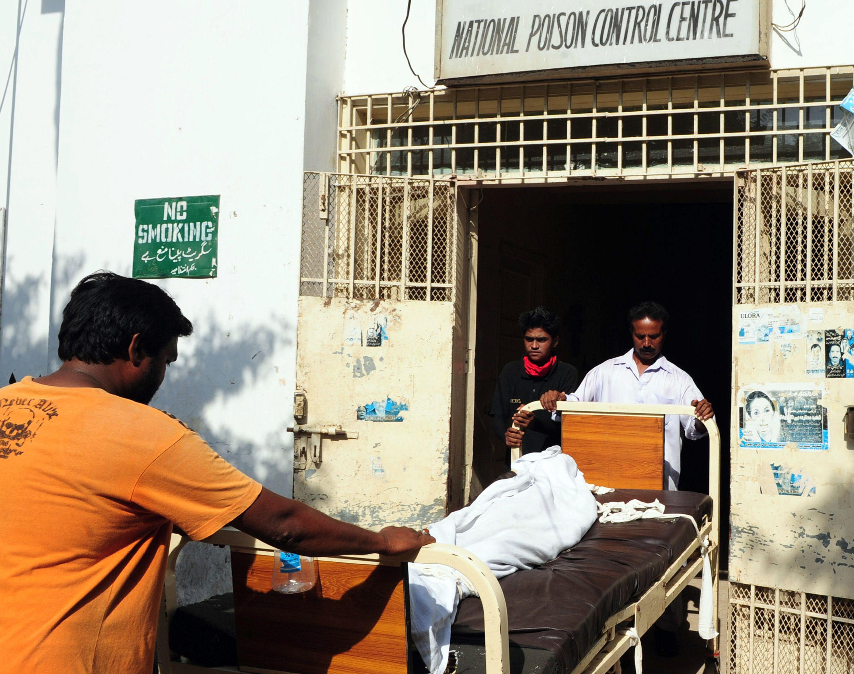 Paramedics move the body of a liquor victim from a hospital in Karachi. PHOTO: AFP