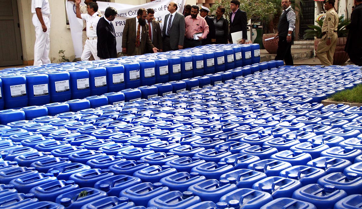 Custom officials display siezed containers of chemicals, used for making liquor, in Ghas Bandar ares. PHOTO: ONLINE